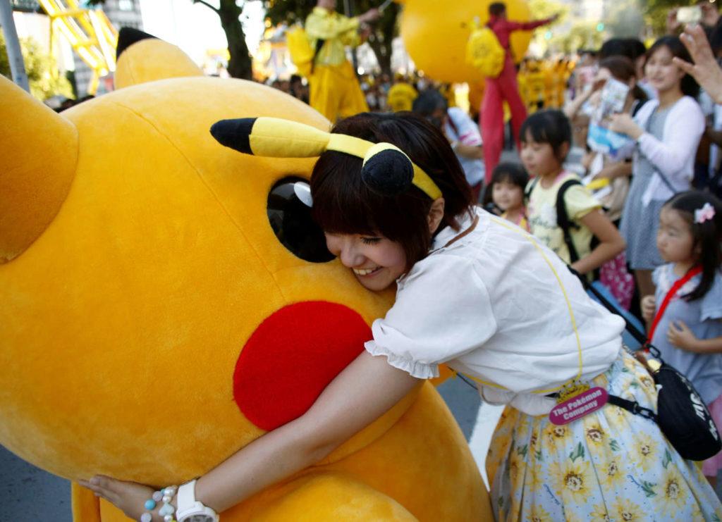 A woman hugs a performer wearing Pokemon's character Pikachu during a parade in Yokohama